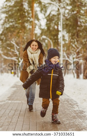 Happy family in winter clothing. Smiling son runs away from his mother outdoor - stock photo