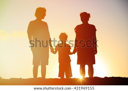 happy family including pregnant mother, father and son at sunset