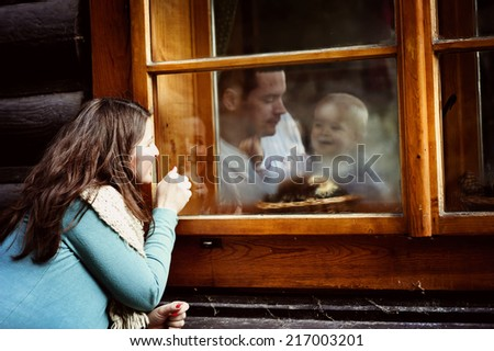 Happy family is enjoying time together. mother is outside looking through the window to her husband and liitle son - stock photo