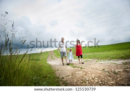 Happy family is playing together in a green meadow. - stock photo
