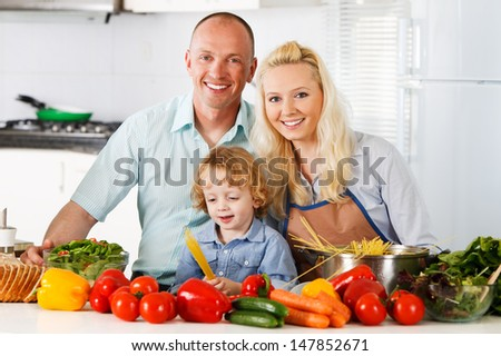 Happy family is preparing a healthy dinner in the kitchen. - stock photo