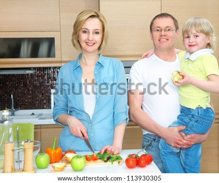 Happy family is preparing a healthy dinner in the kitchen. Mother cuts  vegetables - stock photo