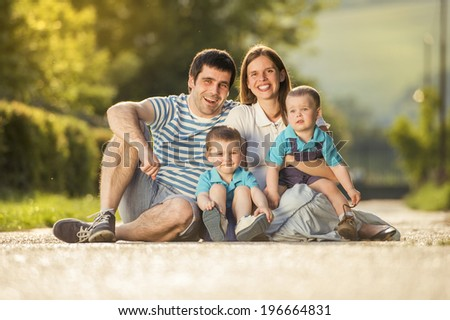 Happy family is relaxing and sitting on countryside road - stock photo