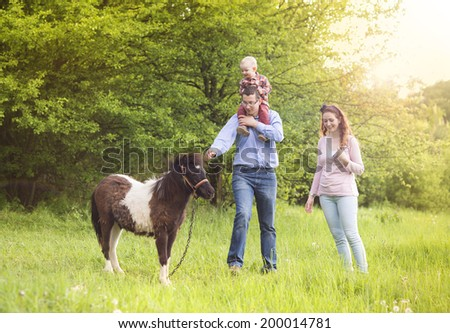 Happy family is relaxing in green meadow with ponny - stock photo