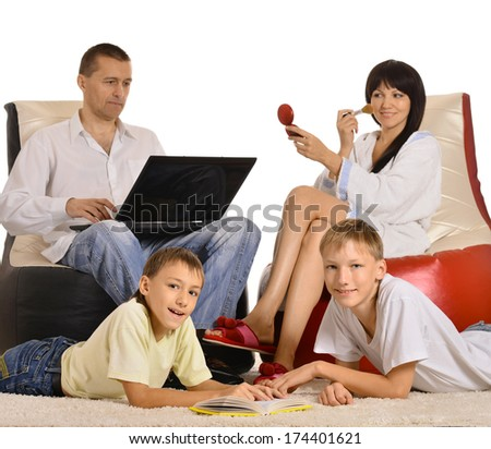 Happy family is resting together at home with laptop