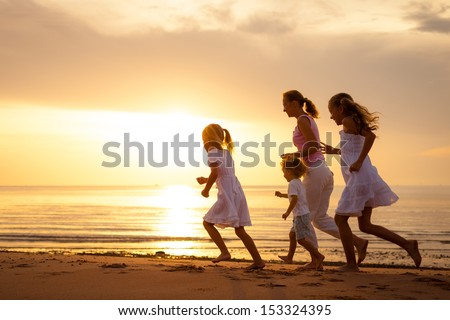 Happy family is running at the beach on the dawn time - stock photo