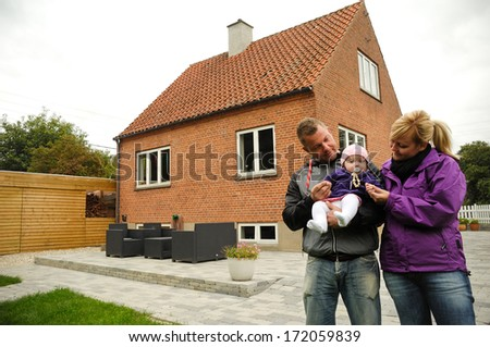 Happy family is standing in front of a house. - stock photo