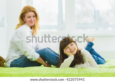 happy family. joyful and dreaming daughter lies beside mom - stock photo