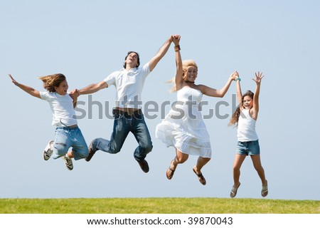 Happy family jumping high against natural background - stock photo