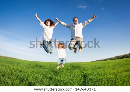 Happy family jumping in green field against blue sky. Summer vacation concept - stock photo