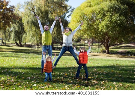 Happy family jumping in the autumn park