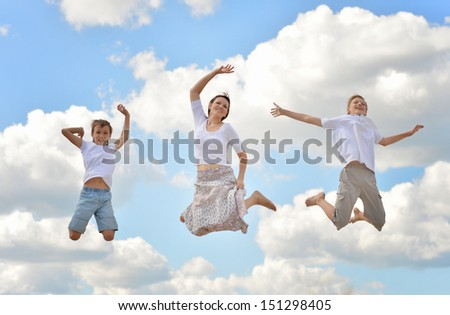 Happy family jumping on a background of blue sky and clouds