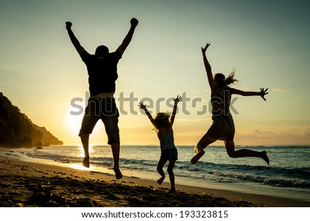Happy family jumping on the beach at the sunrise time