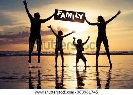 "Happy family jumping on the beach at the sunset time. Parents hold in the hands  inscription ""Family"". Concept of happy family. - stock photo"