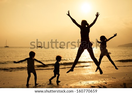 Happy family jumping on the beach on the sunrise time