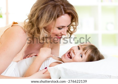 happy family - kid with mother play, laugh and tickle in white bed in bedroom