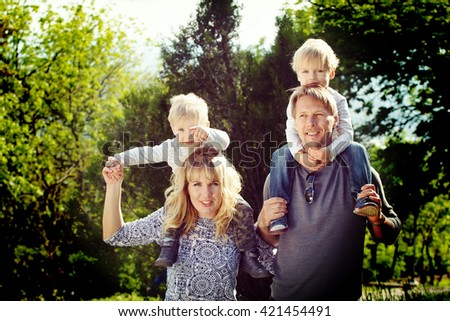 Happy family, kids on parents shoulder. Coloring and processing photos in vintage style with soft selective focus - stock photo