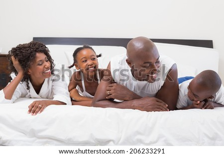 Happy family laughing together in bed at home in the bedroom