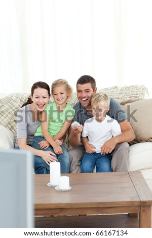 Happy family laughing while watching television sitting on the sofa at home - stock photo