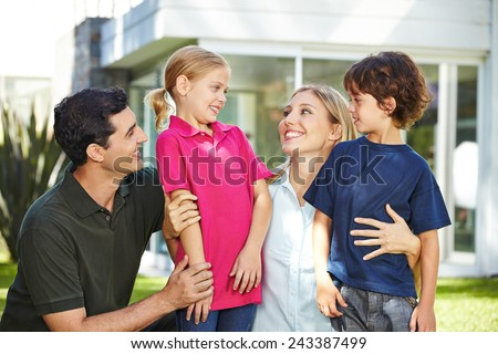 Happy family laughing with two children in garden of a house