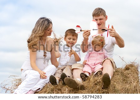 Happy family launching toy aircraft model sitting on haystack together - stock photo
