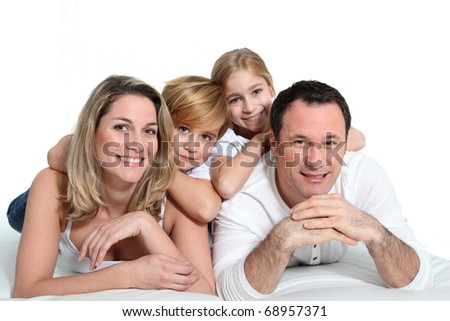 Happy family laying on bed - stock photo
