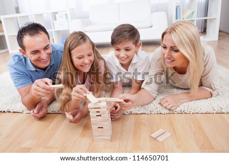 Happy Family Laying On Carpet Playing With The Wooden Blocks At Home - stock photo
