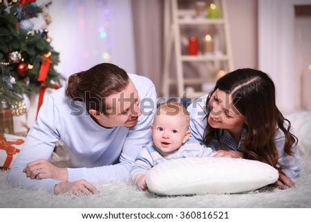 Happy family laying on the floor in the decorated Christmas room - stock photo