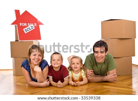 Happy family laying on the floor in their new home - isolated