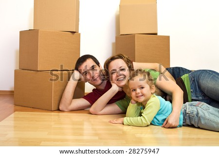 Happy family laying on the floor in their new home with cardboard boxes in the background