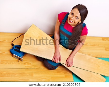 Happy family laying parquet at home. - stock photo