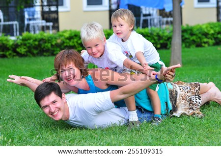 happy family lie on the grass - stock photo