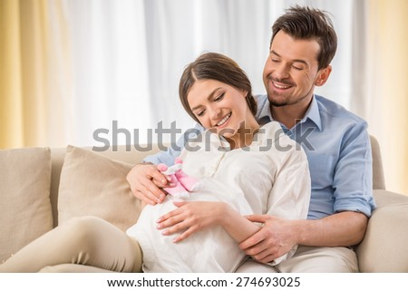 Happy family lifestyle. Young couple are expecting a baby. They are holding a little socks. - stock photo