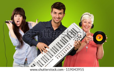 Happy Family Listening To Music On Green Background - stock photo