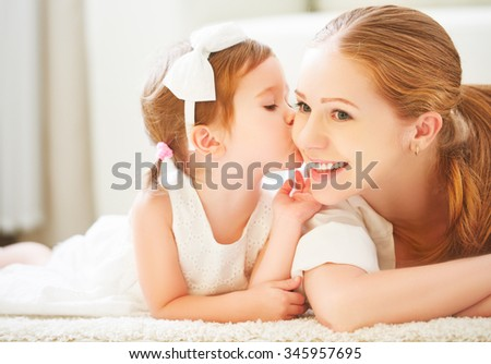 happy family.  Little child girl kisses her mom - stock photo
