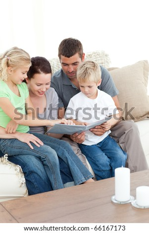 Happy family looking at a photo album sitting together in the living-room at home - stock photo