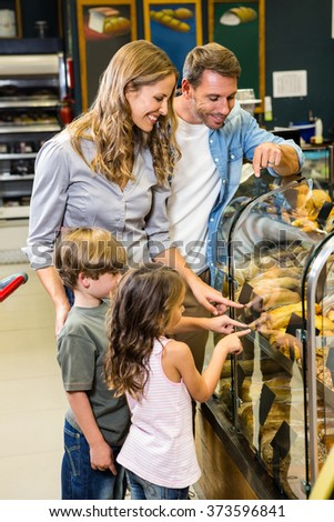 Happy family looking at bread in grocery store - stock photo