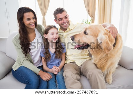 Happy family looking at Golden Retriever while sitting on sofa at home - stock photo