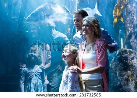 Happy family looking at in a tank at the aquarium - stock photo