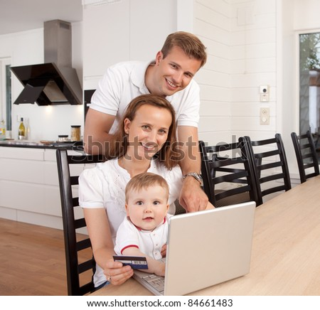Happy family looking at the camera with a smile making an online purchase