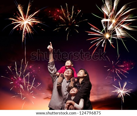 happy family looking fireworks in the evening sky - stock photo