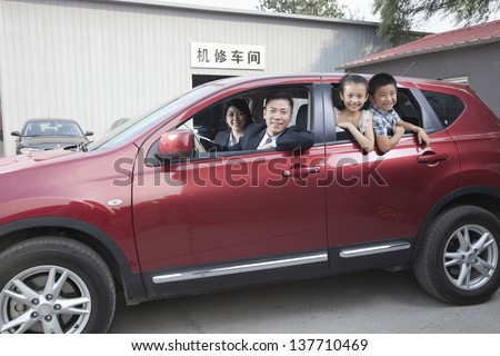 Happy Family Looking Out of a Car - stock photo