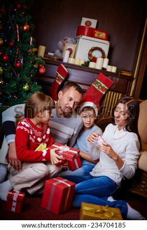 Happy family looking through gifts on Christmas evening at home - stock photo