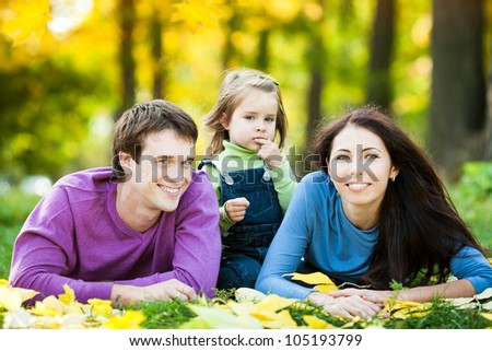 Happy family lying against blurred leaves background in autumn park - stock photo