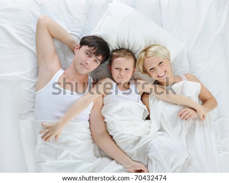 Happy family lying in bed in the morning