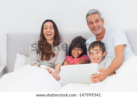 Happy family lying in bed using their laptop at home
