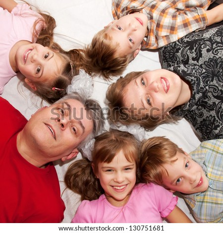 Happy family lying n a circle on the floor. Father, mother and four children smiling.