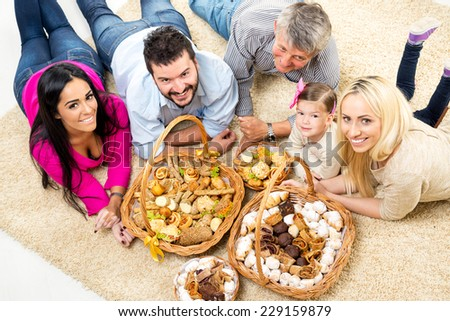 Happy family lying on a carpet in the living room around woven baskets filled with baked goods, looking up with a smile at the camera.