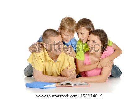 Happy family lying on a floor with books - stock photo