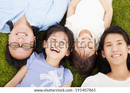 happy family lying on a meadow together - stock photo